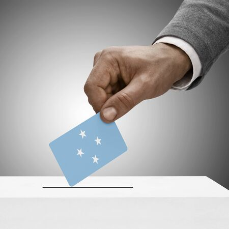 federated: Black male holding Federated States of Micronesia flag. Voting concept