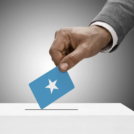 somalian: Black male holding Federal Republic of Somalia flag. Voting concept  Stock Photo