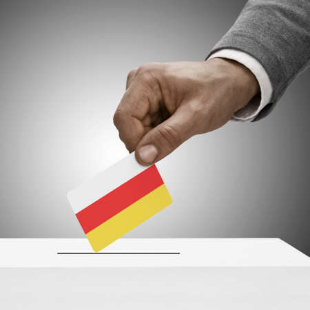 plebiscite: Black male holding South Ossetia flag. Voting concept Stock Photo