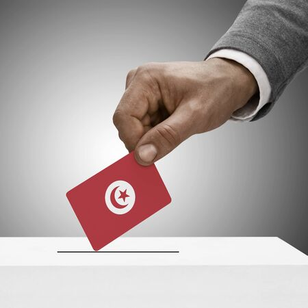 political system: Black male holding Tunisia flag. Voting concept Stock Photo