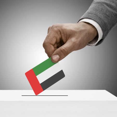 political system: Black male holding United Arab Emirates flag. Voting concept