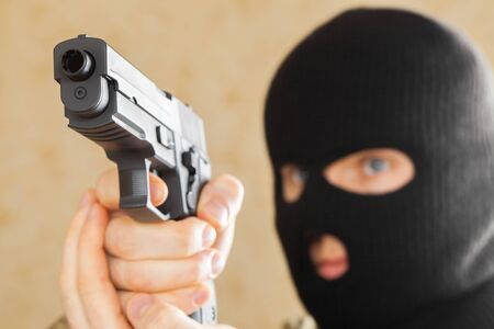 special agent: Man in black mask holding gun and ready to use it Stock Photo