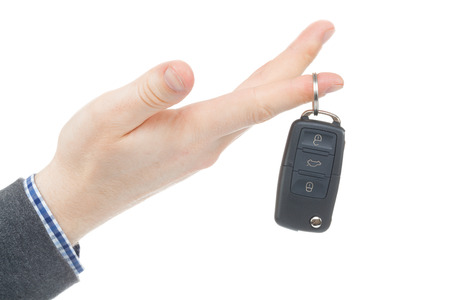 Male hand giving car keys - studio shot isolated on white photo