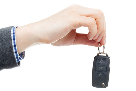 Male hand giving car keys - studio shot over white background photo