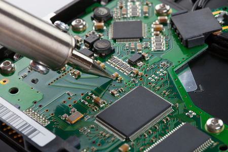 microcircuit: Soldering iron and microcircuit - studio shot