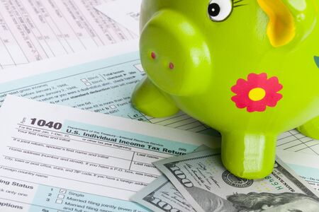 federal tax return: Hundred dollars banknote and piggy bank over US tax form Stock Photo