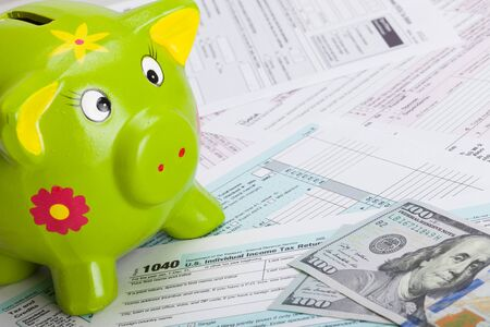 taxable income: Hundred USA dollars banknote and piggy bank over US tax form