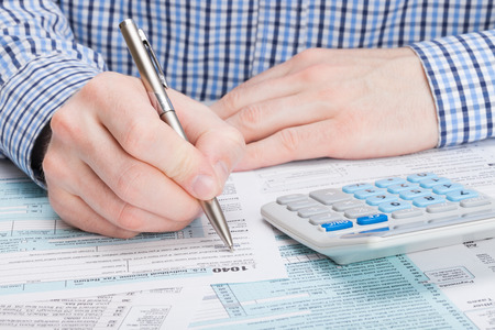tax return: Taxpayer filling out 1040 Tax Form Stock Photo