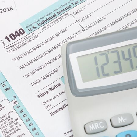 taxpayer: Calculator over US 1040 Tax Form - studio shot Stock Photo