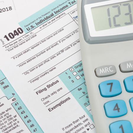 taxable income: US 1040 Tax Form and calculator over it - studio shot