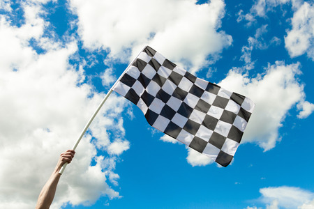 chequered flag: Checkered flag waving in the wind - outdoors shoot