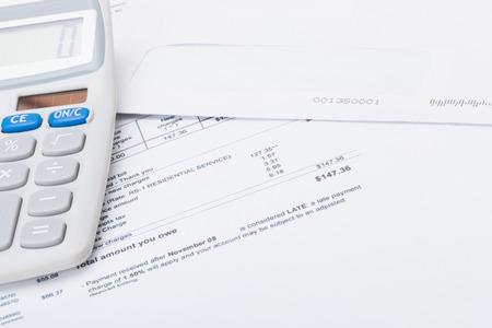 calculator with utility bill under it studio shot stock photo