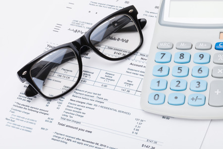 Calculator and glasses with utility bill under it - studio shot