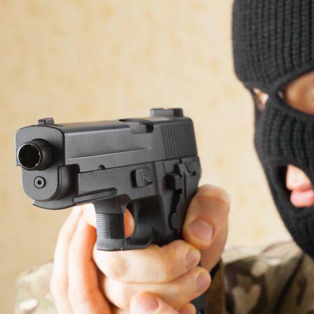 Man in black mask holding gun before him photo