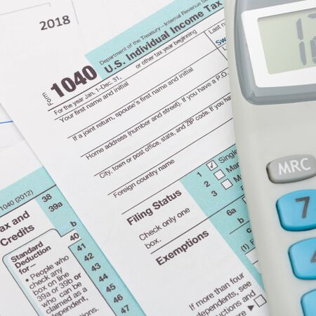 taxable income: US 1040 Tax Form and calculator over it Stock Photo