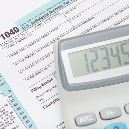 tax form: Calculator over US 1040 Tax Form