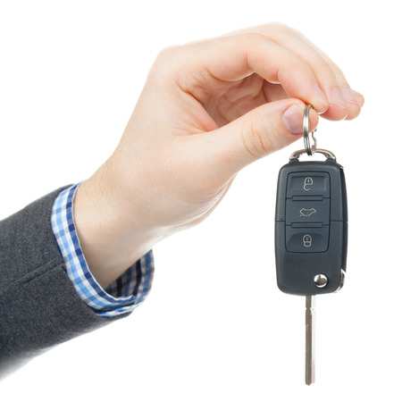 passing over: Male hand giving car keys - studio shot isolated on white background