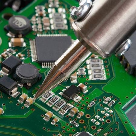 microcircuit: Studio shot of soldering iron and microcircuit