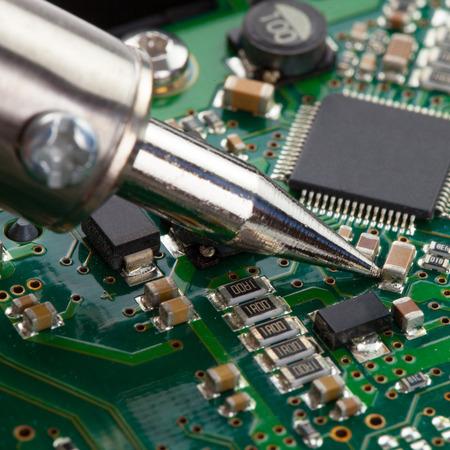 microcircuit: Close up studio shot of soldering iron and microcircuit