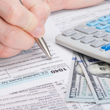 taxpayer: Taxpayer filling out USA 1040 Tax Form - studio shot