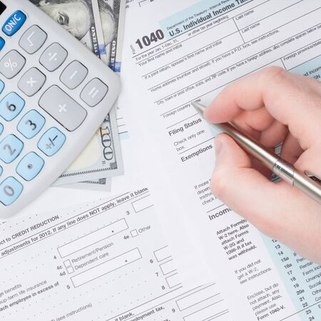 filling out: Taxpayer filling out USA 1040 Tax Form Stock Photo