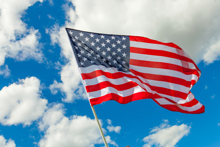 Amerikaanse vlag en cumuluswolken erachter Stockfoto