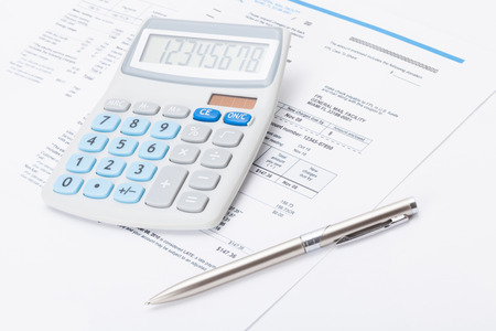 utility payments: Calculator with silver pen and utility bill under it