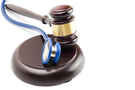 Wooden judge gavel and stethoscope next to it Stock Photo