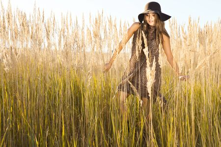 wilds: Beautiful lady model wandering through meadow wilds at midday Stock Photo