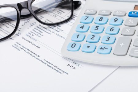 utility payments: Glasses and calculator over utility bill Stock Photo