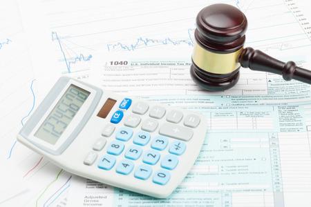 Judge's gavel and calculator over US 1040 Tax Form Фото со стока