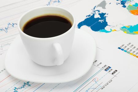 financial market: Coffee cup over world map and financial market chart