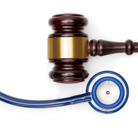 misbehavior: Wooden judge gavel, pills bottle and stethoscope on white backround - studio shot