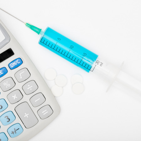 Calculator and a syringe - studio shot Stock Photo