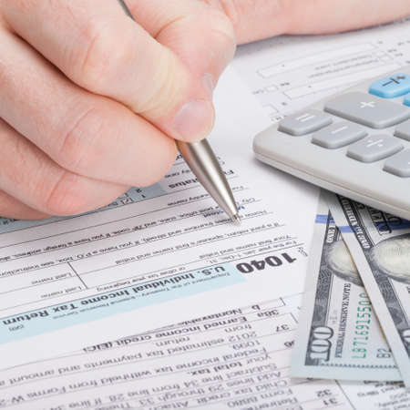 taxpayer: Taxpayer filling out USA 1040 Tax Form - close up shot