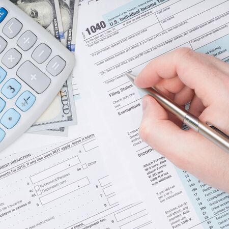 filling out: Taxpayer filling out U.S. 1040 Tax Form - studio shot