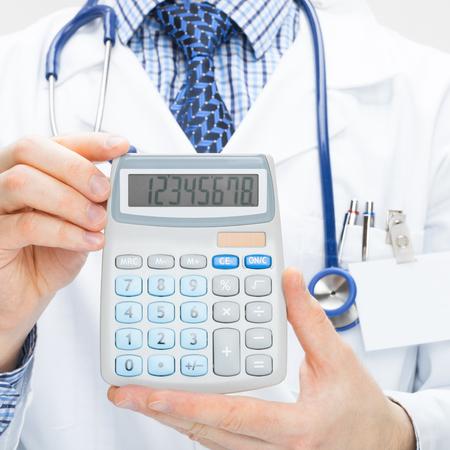 Medical doctor holding calculator in hands - health care concept Banco de Imagens