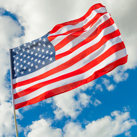 Neat USA flag and cumulus clouds on background