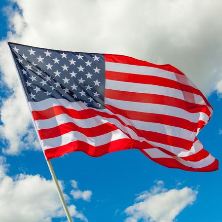 Nette Amerikaanse vlag en cumulus wolken achter Stockfoto