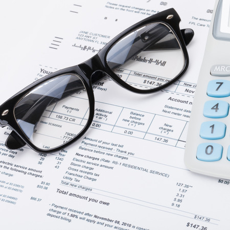 utility payments: Calculator, glasses and utility bill under it - close up shot Stock Photo