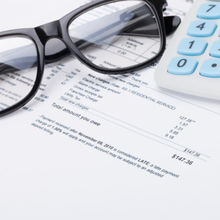 utility payments: Calculator with pen, glasses and utility bill under it - close up shot Stock Photo