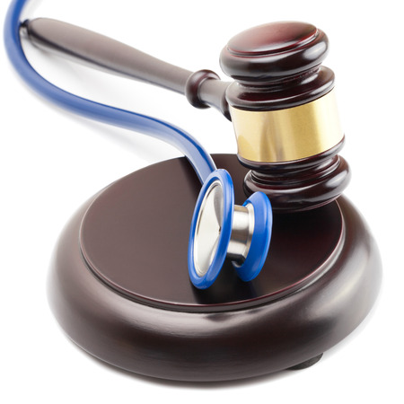 misbehavior: Wooden judge gavel and stethoscope next to it - close up shot Stock Photo