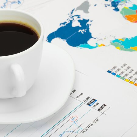 financial market: Coffee cup over world map and financial market chart - close up shot Stock Photo