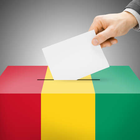 polling booth: Ballot box painted into national flag colors - Guinea Stock Photo
