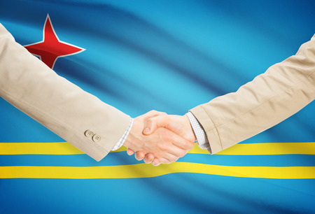 aruba flag: Businessmen shaking hands with Aruba flag on background