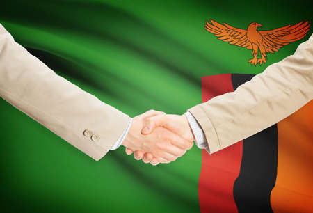 zambia flag: Businessmen shaking hands with Zambia flag on background