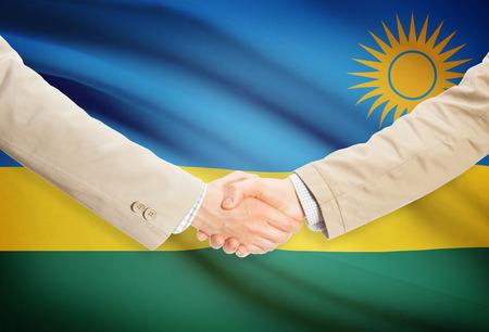 Businessmen shaking hands with Rwanda flag on background