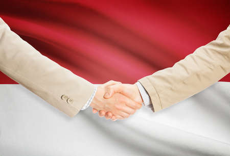 monegasque: Businessmen shaking hands with Monaco flag on background