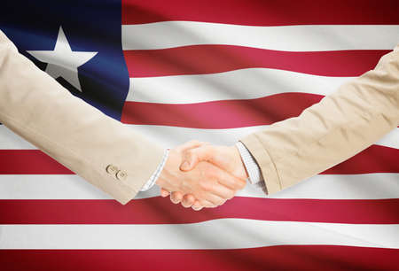 Businessmen shaking hands with Liberia flag on background photo