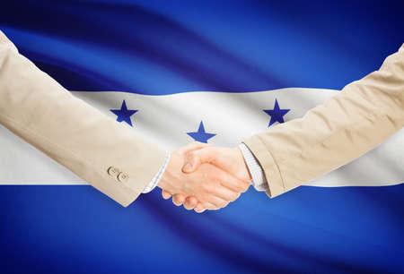 Businessmen shaking hands with Honduras flag on background photo
